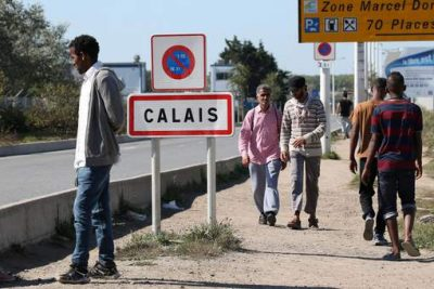 "Migrants pass by a road sign as they leave the northern area of the camp called the ""Jungle"" in Calais, France, September 7, 2016.  REUTERS/Charles Platiau"